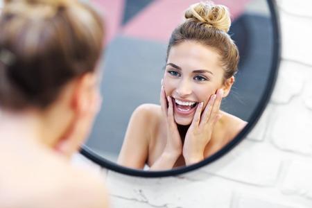 Mujer joven, limpieza, cara, en, cuarto de baño, espejo Foto de archivo
