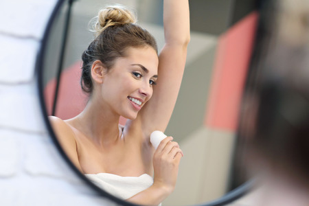 Young woman using deodorant in bathroom Stock Photo