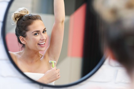 Young woman shaving armpits in bathroom Stockfoto