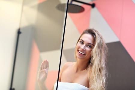 Beautiful blonde Caucasian woman posing in bathroom with wet hair
