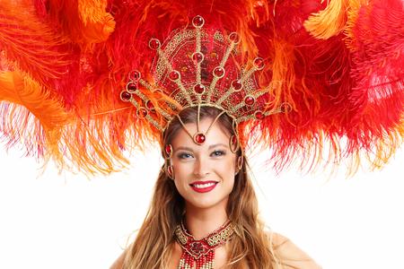 Brasilianische Frau posiert im Samba-Kostüm auf weißem Hintergrund