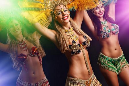 Brazilian women dancing samba over black background