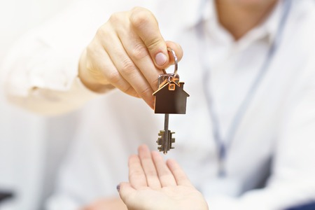 Midsection of real estate agent and buyer hands with keys Reklamní fotografie