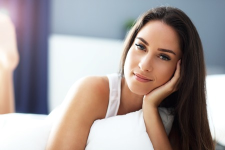 Young beautiful woman waking up in her bed fully rested Stock Photo