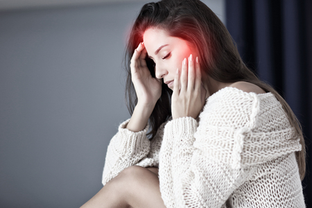 Adult woman suffering from headache at home