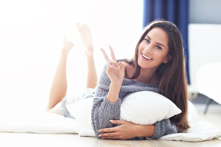 Young beautiful woman lying on bed in the morning Standard-Bild