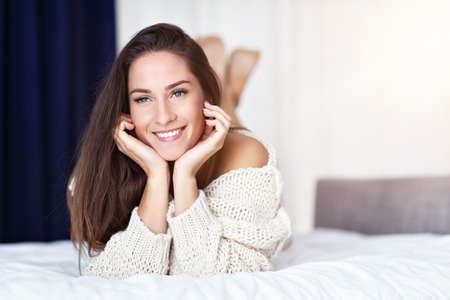 Young beautiful woman lying on bed in the morning Stock Photo