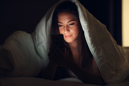 Young beautiful woman resting in bed with smartphone Stock Photo