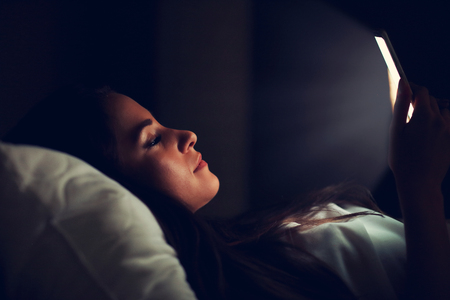 Young beautiful woman resting in bed with smartphone Stockfoto