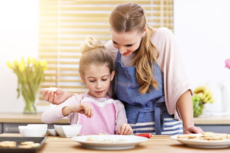 Mother and daughter preparing cookies in the kitchen Banque d'images - 116994327
