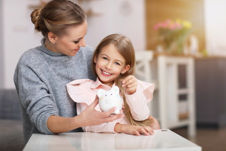 Young girl and her mother with piggybank sitting at table Banco de Imagens
