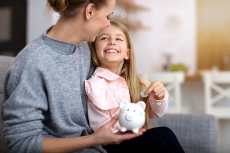 Young girl and her mother with piggybank sitting at table Imagens
