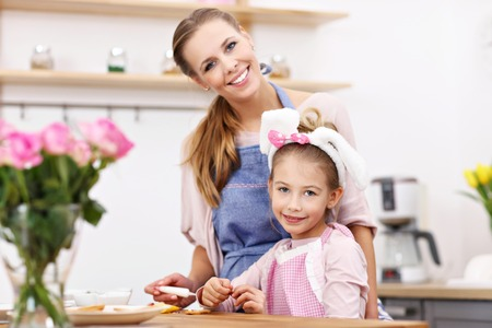 Little girl and her mom in aprons having fun in the kitchen Stock Photo
