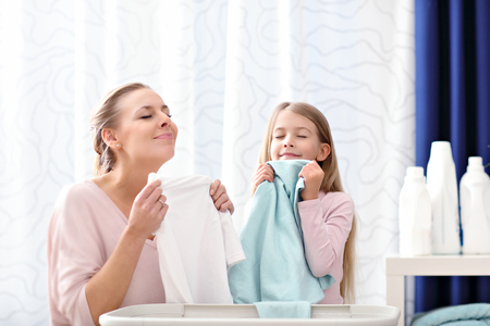 Beautiful young woman and child girl having fun while doing laundry at home
