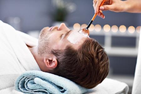 Hombre guapo con facial en el salón de spa