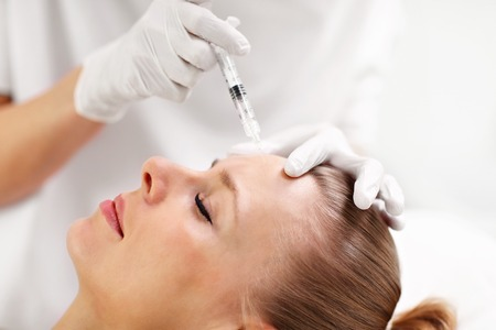 Close up of hands of cosmetologist making  injection in female forehead