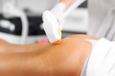 Beautician Giving Epilation Laser Treatment To Woman On Buttocks