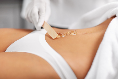 Beautician Giving Epilation Laser Treatment To Woman On Belly