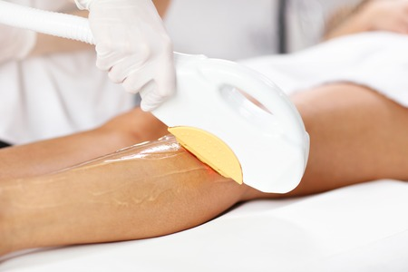 Beautician Giving Epilation Laser Treatment To Woman On Legs Stock Photo