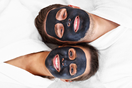 Glückliches Paar mit Gesichtsbehandlung im Spa-Salon