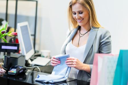 Asistente de ventas en tienda de ropa Foto de archivo