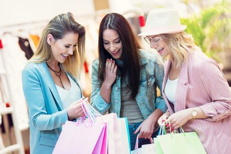 Imagen de un grupo de amigos felices comprando ropa en el centro comercial