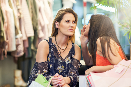 Girl friends shopping for clothes in store Stock Photo