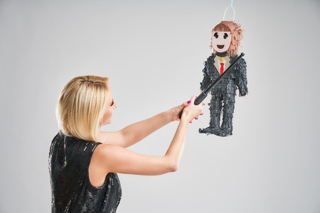 Woman hitting male pinata over grey background