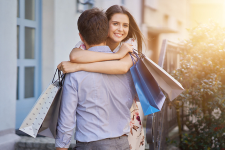 Portrait of happy couple with shopping bags in city smiling and huging. Фото со стока