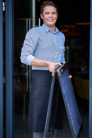 Portrait of waiter opening restaurant in summer