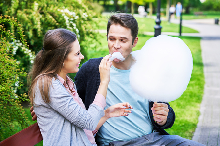 Young couple strolling in the park and eating cotton candy