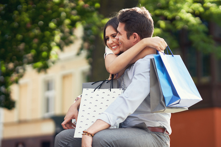 Portrait of happy couple with shopping bags in city smiling and hugging. Фото со стока