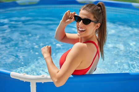 Close up view of attractive woman relaxing on swimming pool in the backyard Фото со стока
