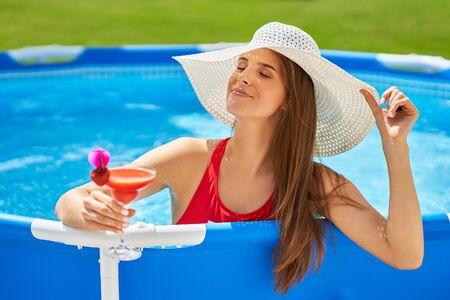 Vista ravvicinata di una donna attraente che si rilassa sulla piscina nel cortile sul retro