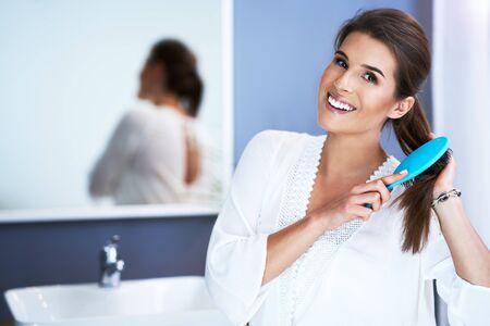 Happy woman brushing hair in bathroom