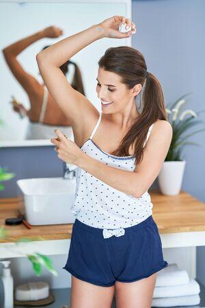Schöne brünette Frau mit Deo im Badezimmer Standard-Bild