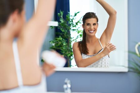 Beautiful brunette woman using deodorant in the bathroom Archivio Fotografico