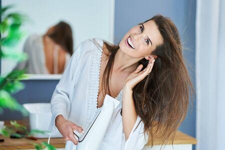 Happy woman drying her hair in bathroom