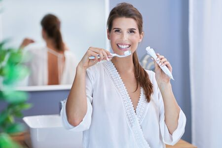 Beautiful brunette woman brushing teeth in the bathroom