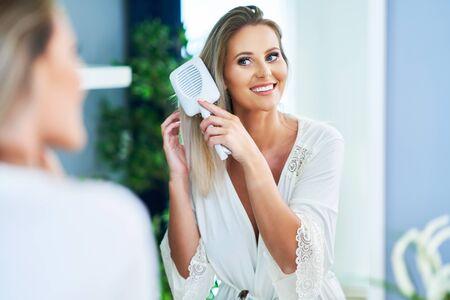 Adult woman brushing her hair in bathroom