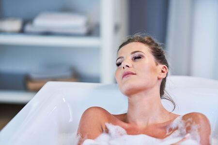 Portrait of a young woman relaxing in the bathtube