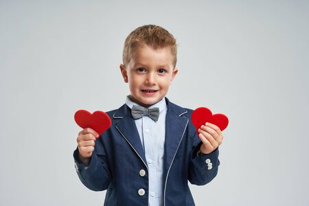 Portrait of a happy cute little kid holding red heart and looking at camera isolated over gray background