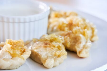Picture of fried dumplings stuffed with meat sprinkled with carmelized onion on a white plate