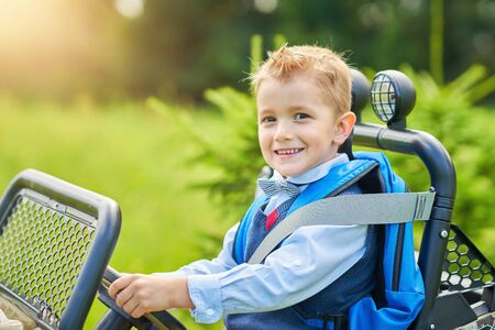 Picture of school boy driving kids car with backpack