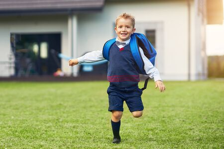 Happy little preschool kid boy with backpack posing outdoors Stockfoto