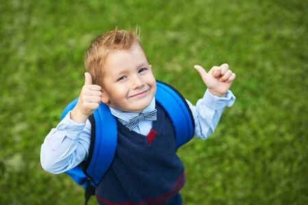 Happy little preschool kid boy with backpack posing outdoors Stock Photo