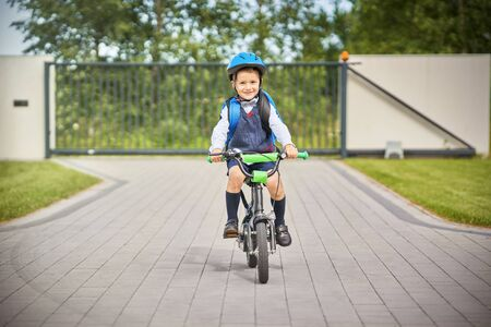 School boy in safety helmet riding bike with backpack