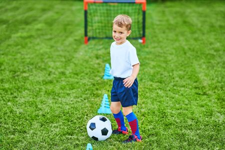 Little Boy practising soccer outdoors