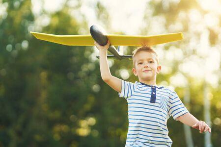 Glücklicher 3-jähriger Junge, der Spaß hat, mit dem großen Flugzeug im Freien zu spielen?
