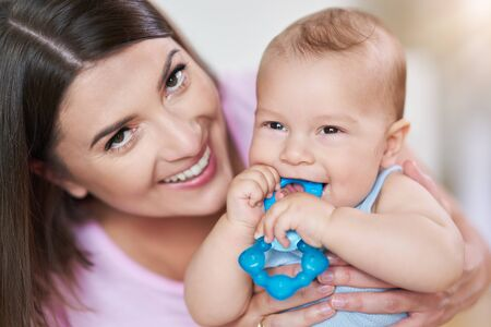 Mother and her Newborn Baby with teething ring